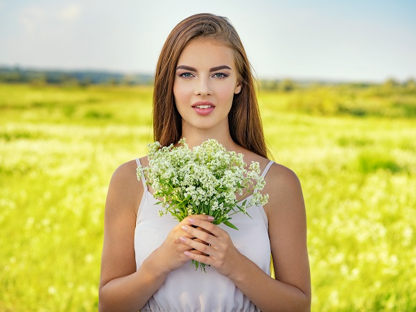 Happy and smiling beautiful Russian woman outdoor with flowers in hands