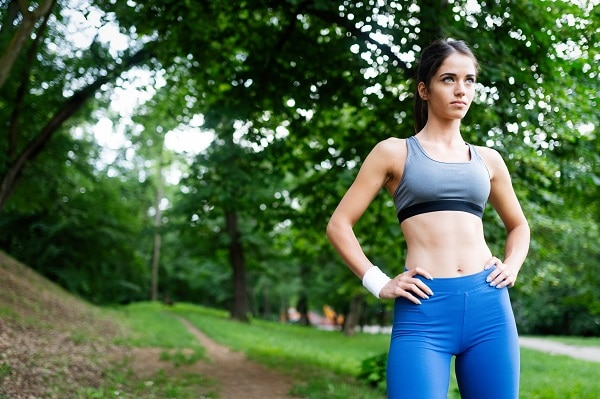 Healthy lifestyle image of a young Russian woman exercising in the green park outside
